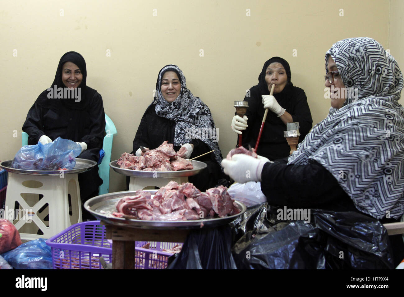 Members of Bahrain's Shia community preparing food for a communal meal. - Stock Image