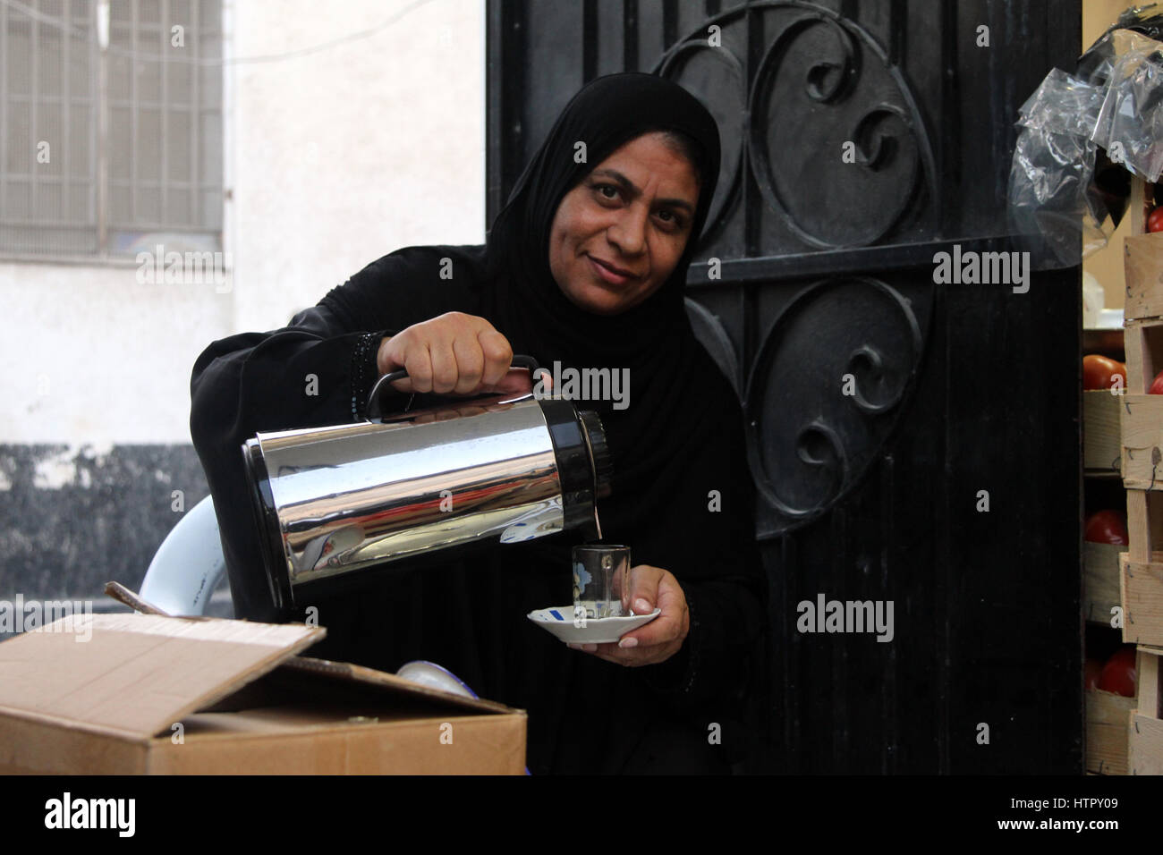 A Bahraini Shia woman, wearing the traditional black abaya, pours a cup of tea. - Stock Image
