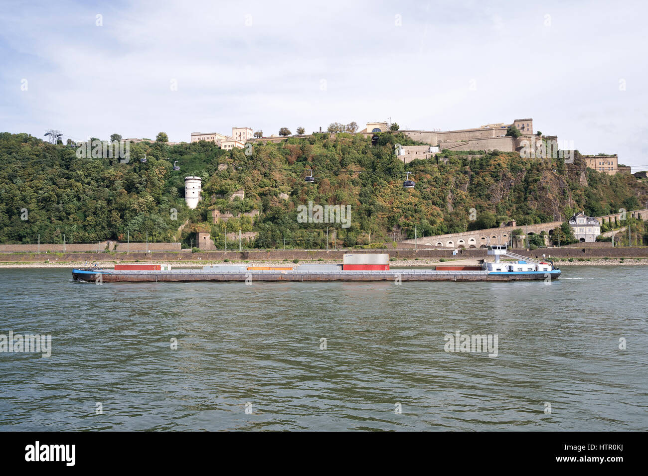 inland container vessel passing fortress Ehrenbreitstein in Koblenz/ Germany - Stock Image
