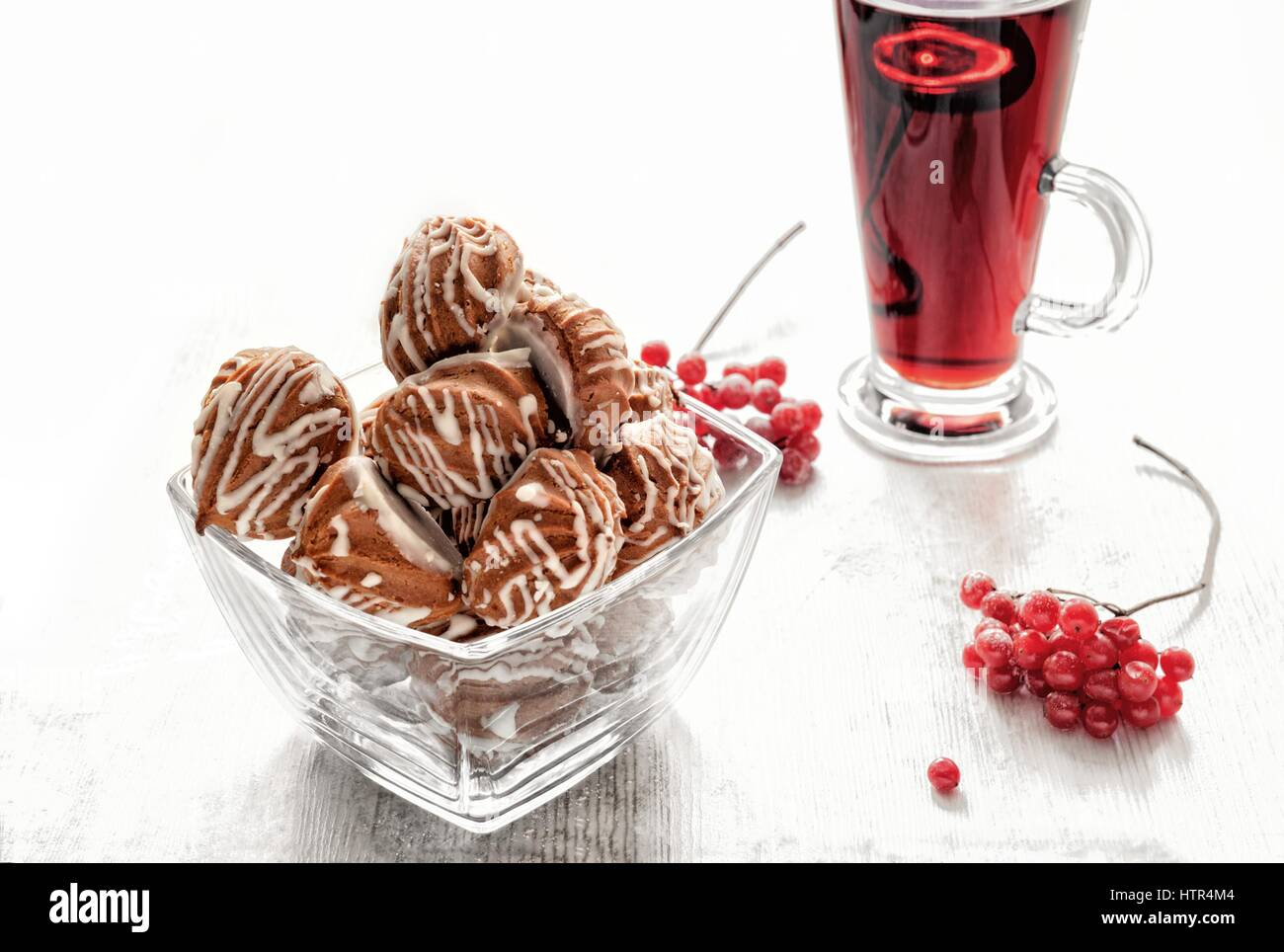 profiteroles, biscuits, stuffed with berry jam, round, with tea in clear glass cups - Stock Image