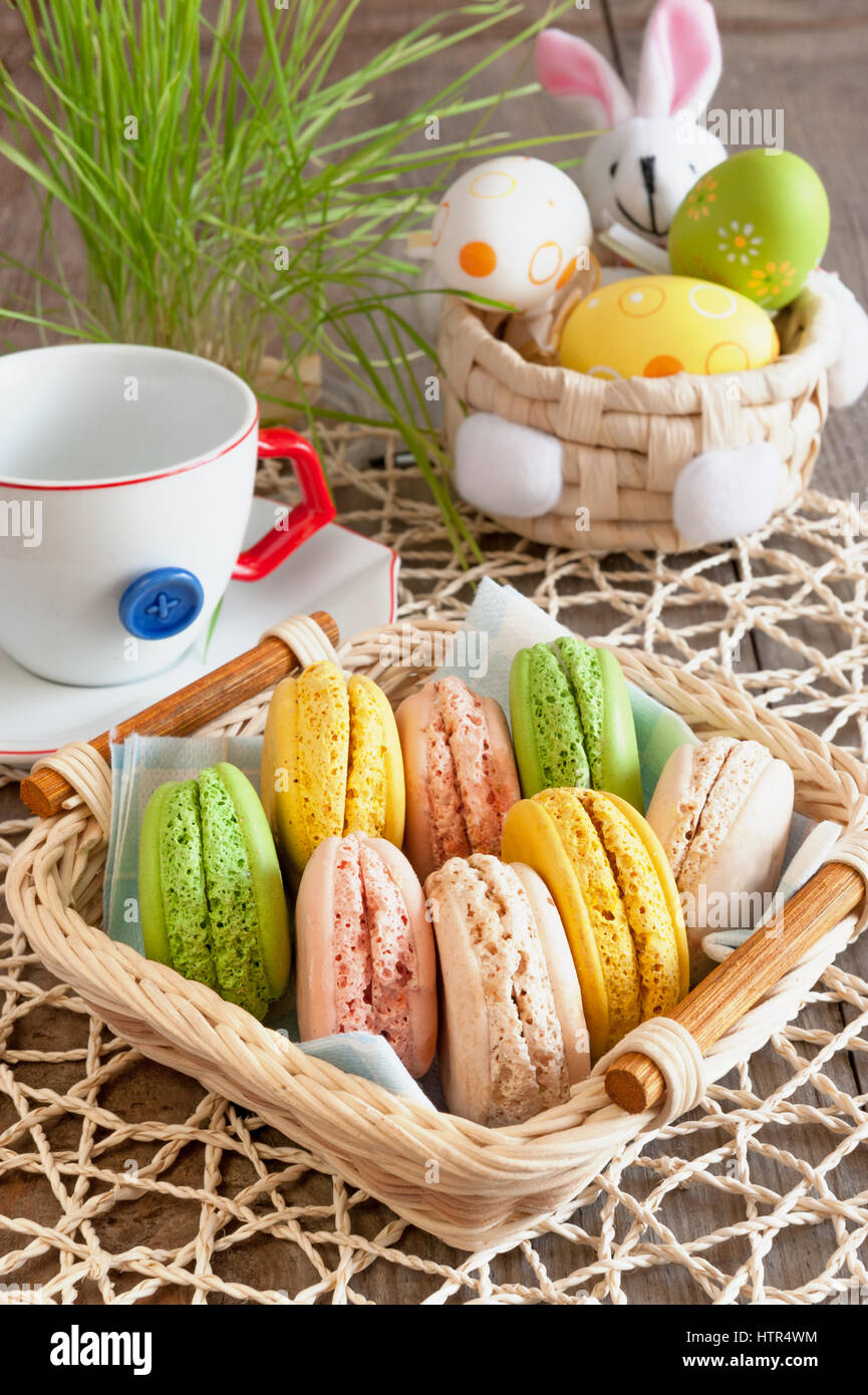 multicolored meringues macaroons in a basket for Easter - Stock Image