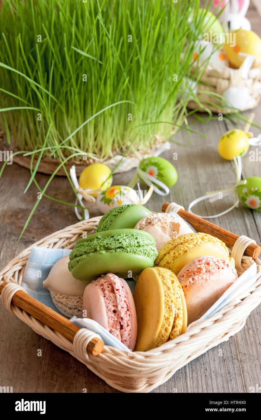 multicolored meringues macaroons in a wicker basket Easter eggs - Stock Image