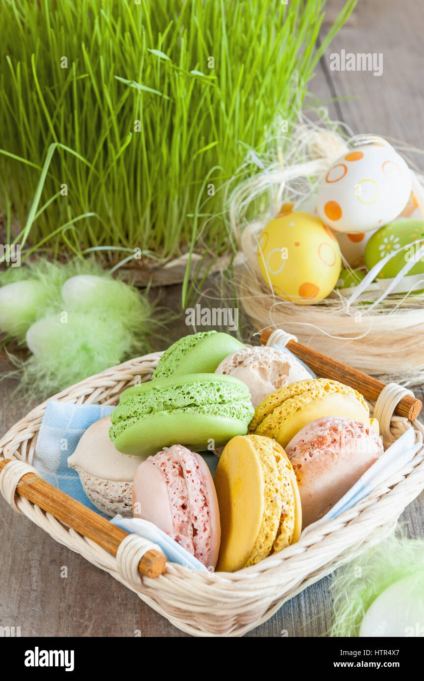 multicolored meringues macaroons in a wicker basket of Easter eggs on a grass background for Easter - Stock Image