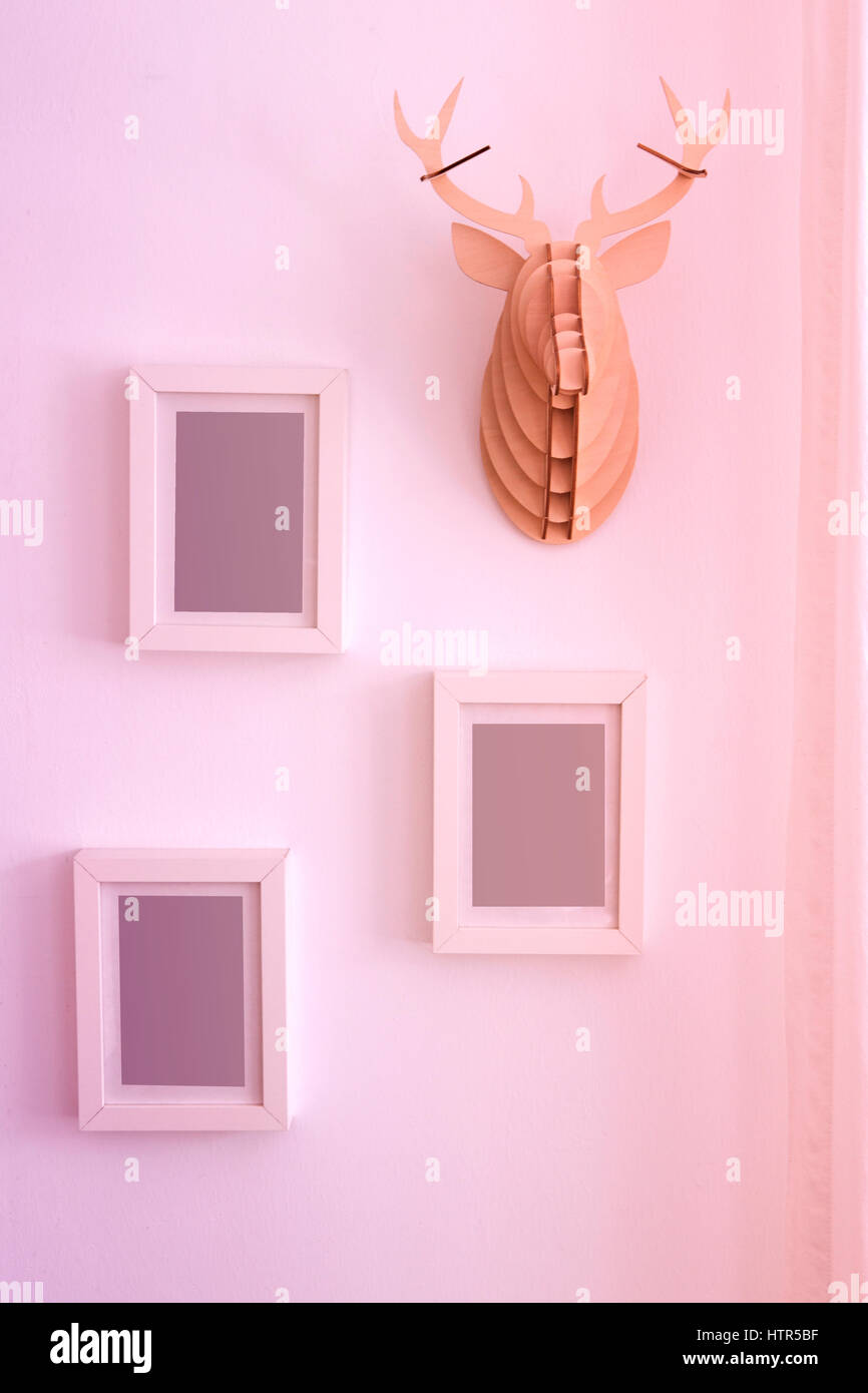 three empty picture frames on wall next to decorative fake antler ...