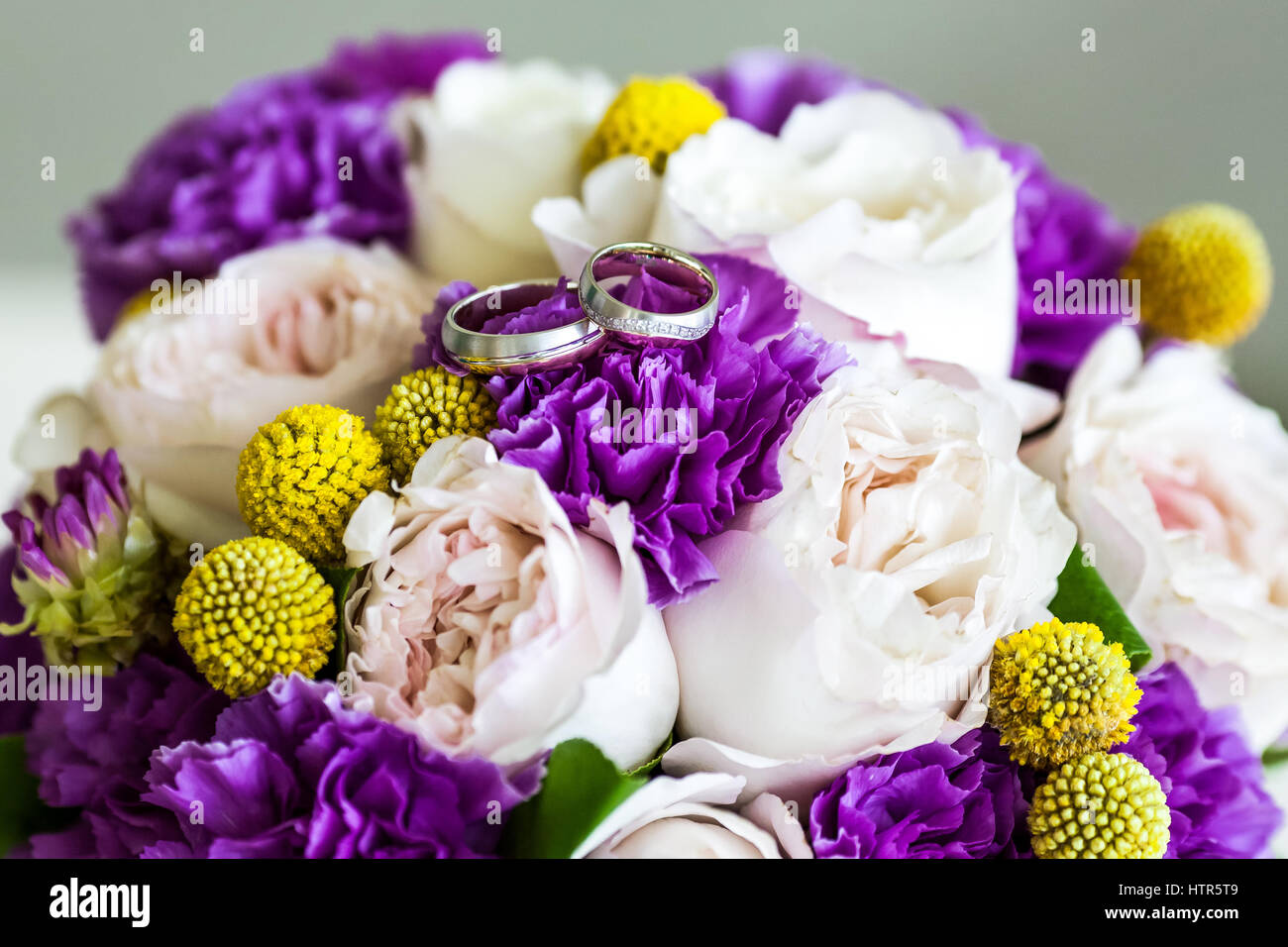 Wedding Rings On Bouquet Of Pink And Purple Flowers In Blue Vase