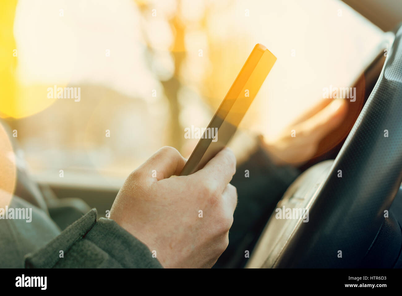 Reckless traffic behavior, driving and using mobile phone to send SMS message - Stock Image