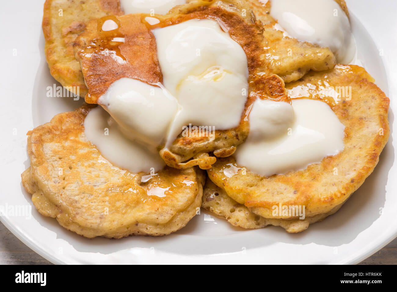 small individual scotch pancakes served on a white plate with yoghurt and honey - Stock Image