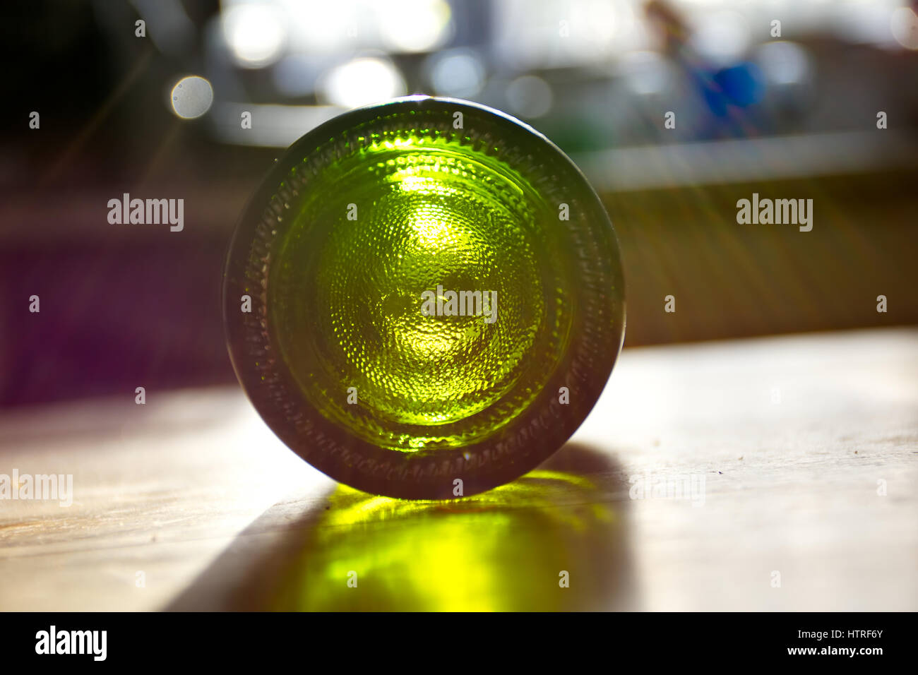 The morning after,empty bottle of wine rolling on table after party. - Stock Image
