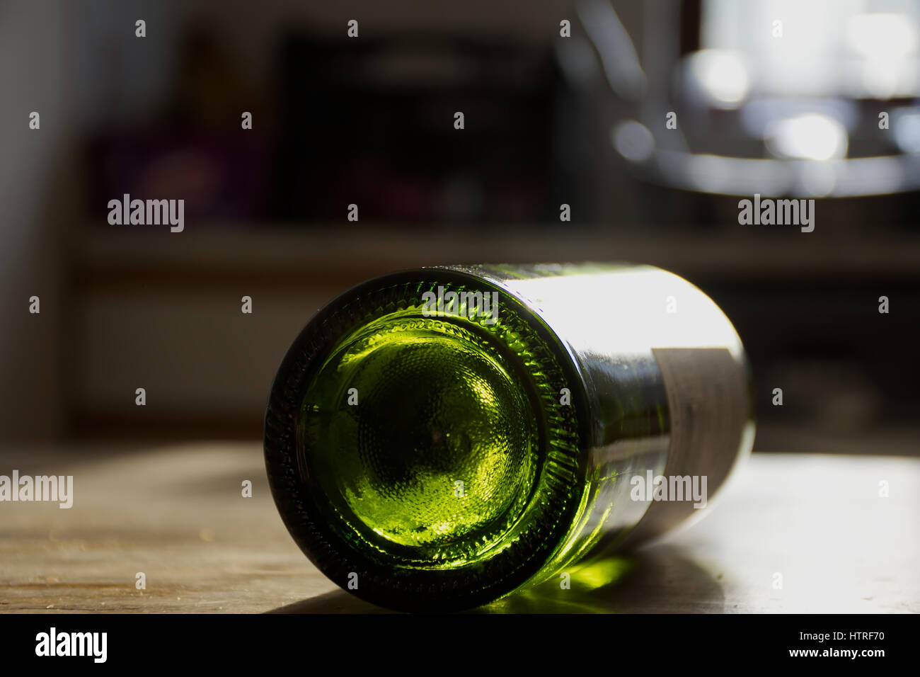 Wine bottle rolling on table after house party in university students accomodation. - Stock Image
