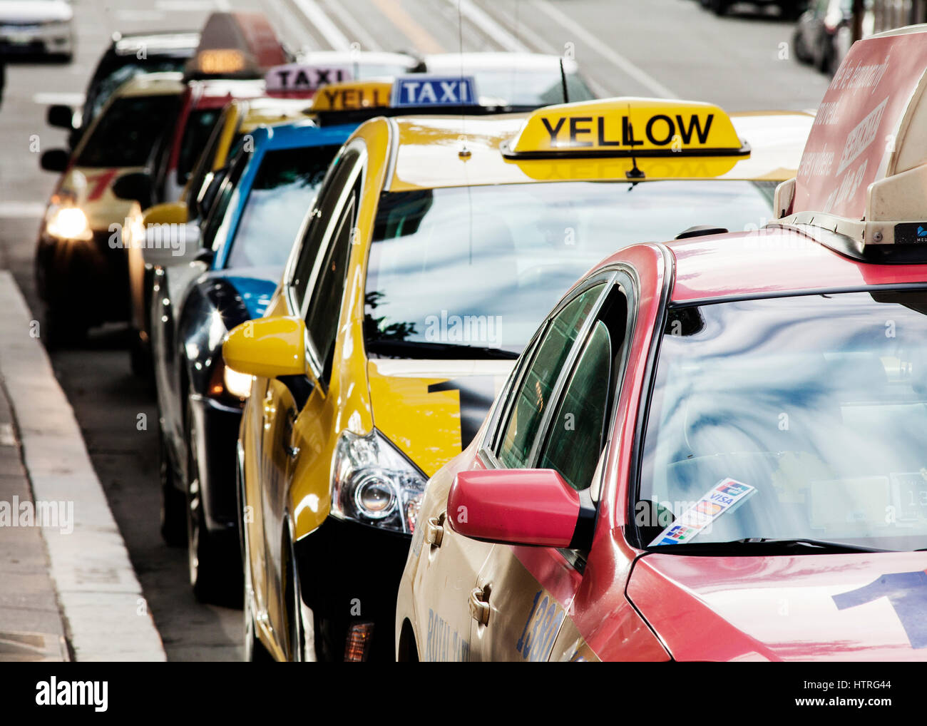 A row of colorful taxis. - Stock Image