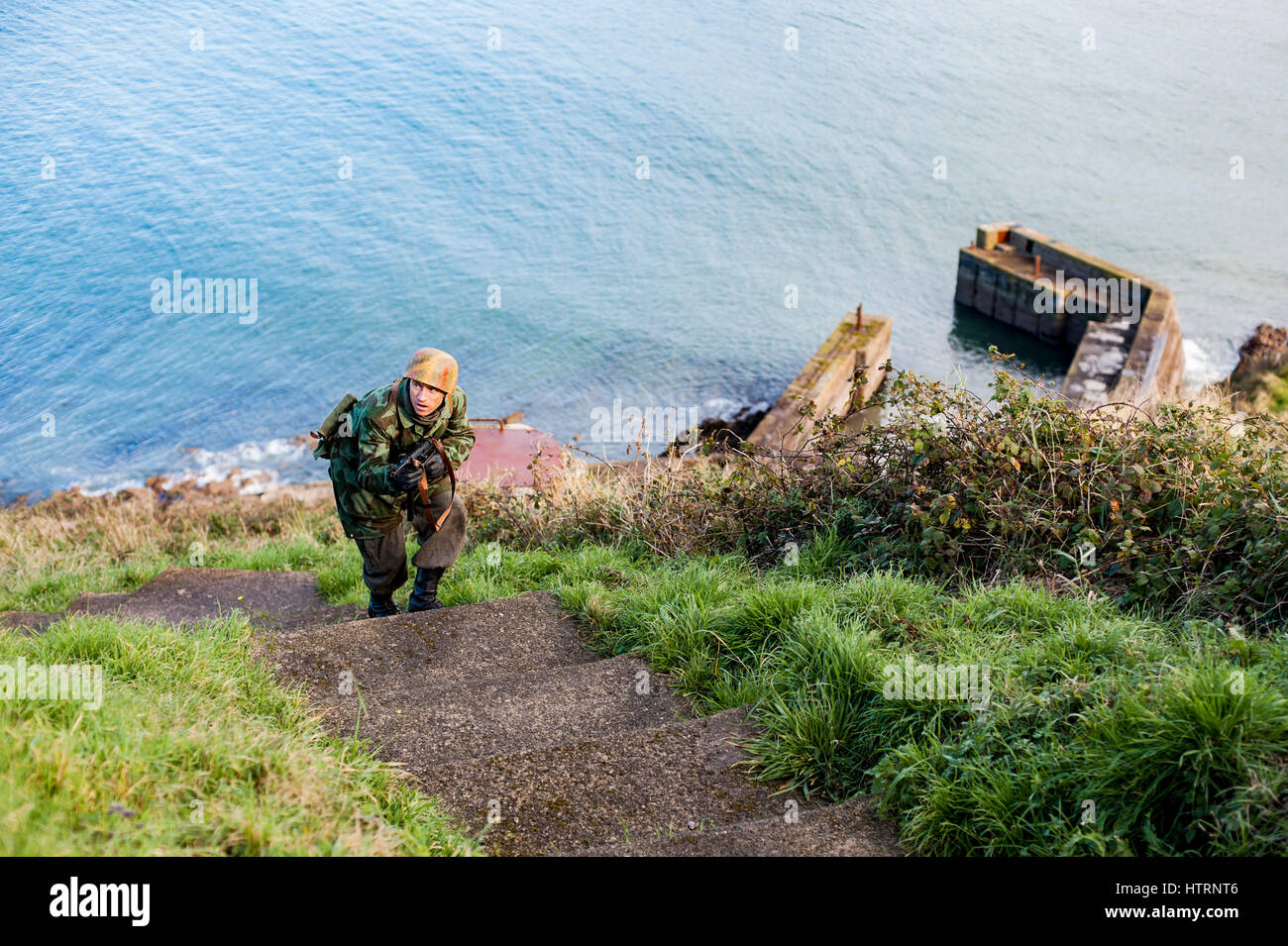 Re-enactor portraying a German Fallschirmjager/parachutist ascends steps at Fort Camden, Coumty Cork, Ireland during - Stock Image