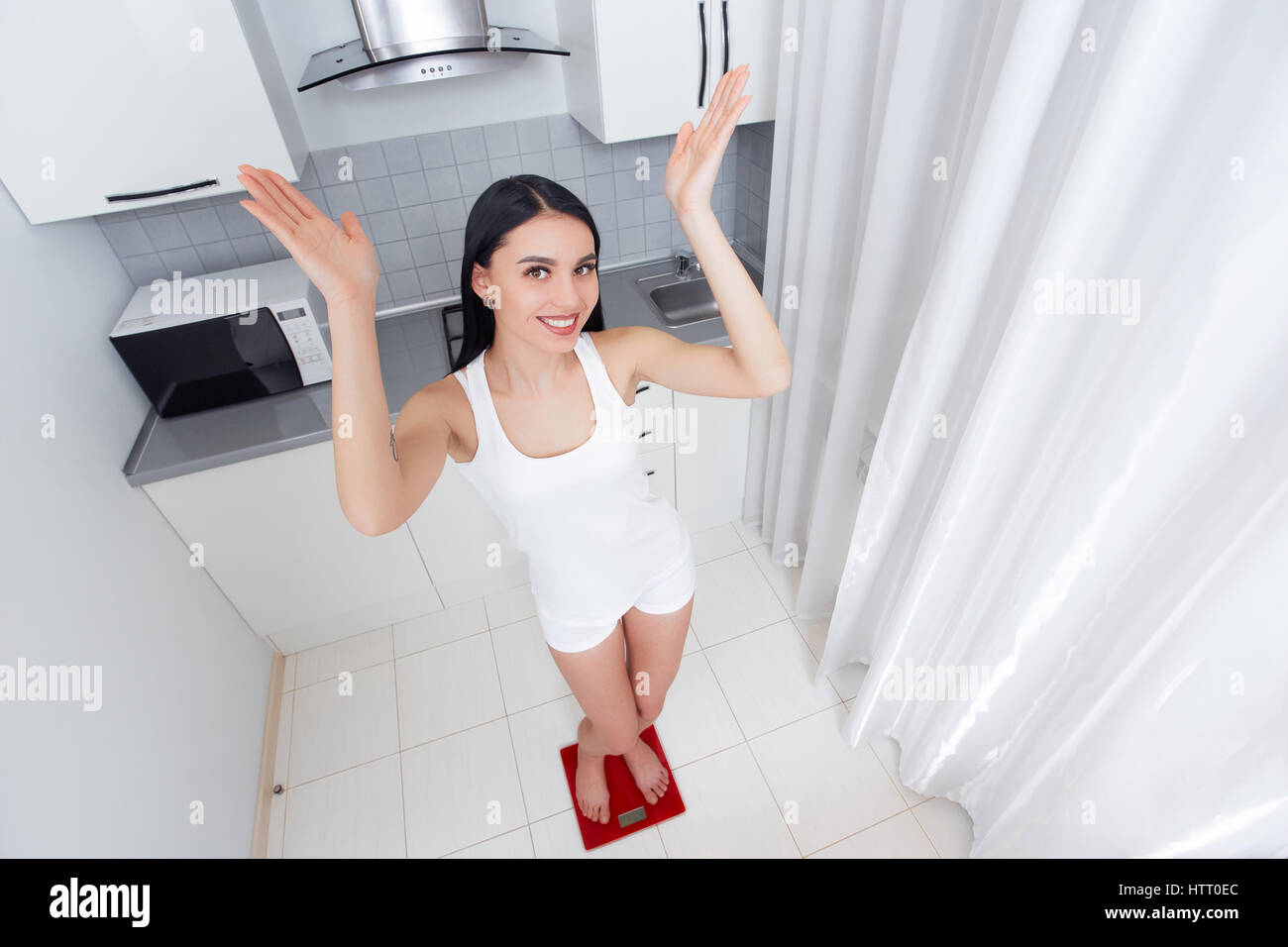 Happy woman weighing in morning and happy smiling, gesturing by hands rise up and looking at camera. Brunette pretty - Stock Image
