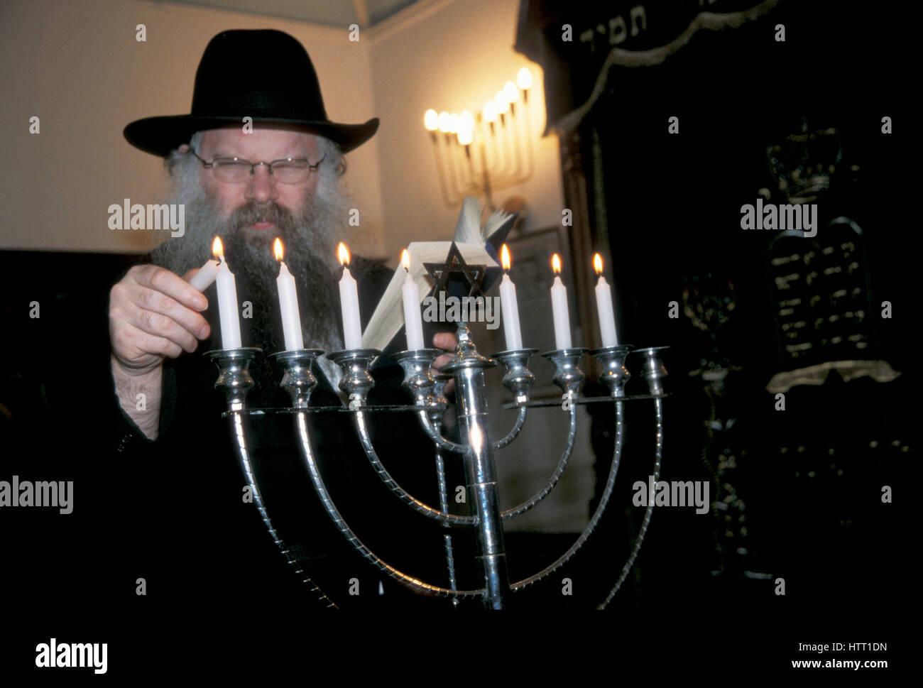 Rabbi lighting menorah Hanukah Stamford Hill North London - Stock Image