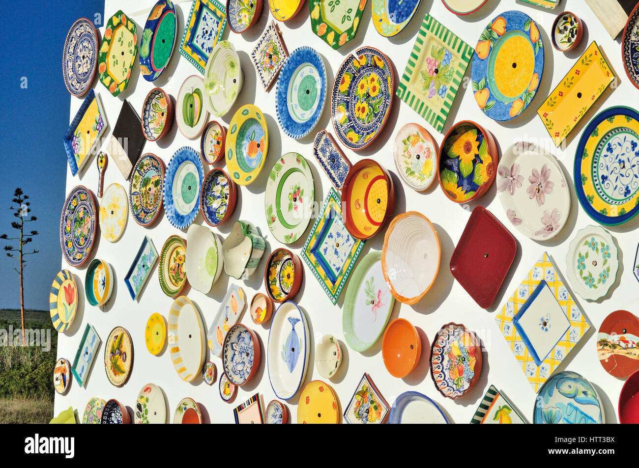 Colorful ceramic plates at a white washed wall - Stock Image