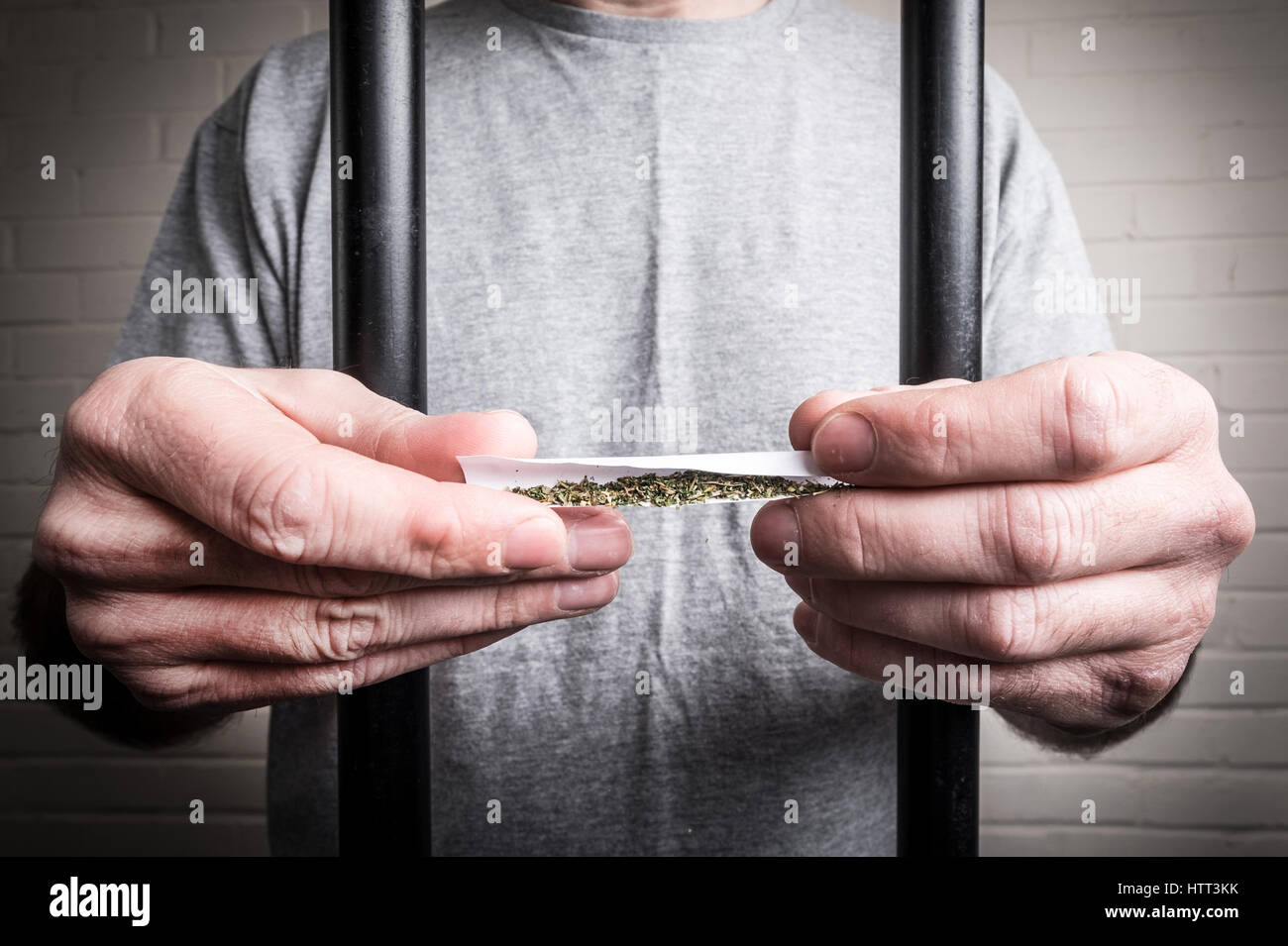 A prisoner behind bars in prison holding drugs or legal highs Spice  (photo posed by model to illustrate the issue - Stock Image