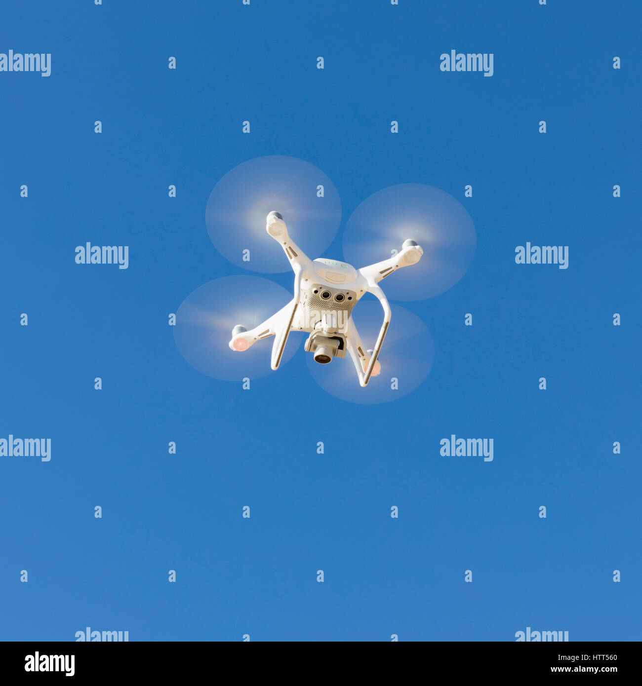 DJI Phantom 4 drone with camera in flight. - Stock Image