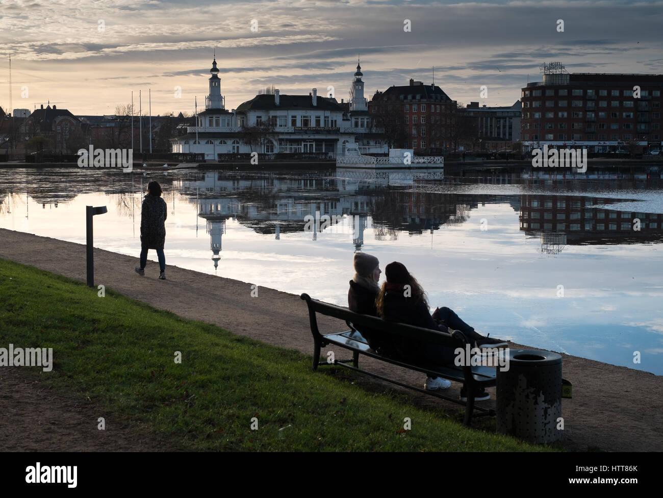 Couple on bench enjoying evening sun Peblinge Sø ('The Lakes'),  `thr Lake Pavilion in the background, - Stock Image