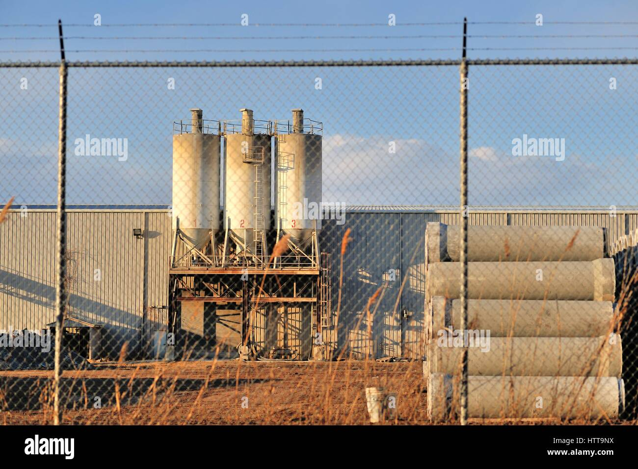 A manufacturing business secured behind a chain link fence, topped by barb wire in this industrial setting in Bartlett, - Stock Image