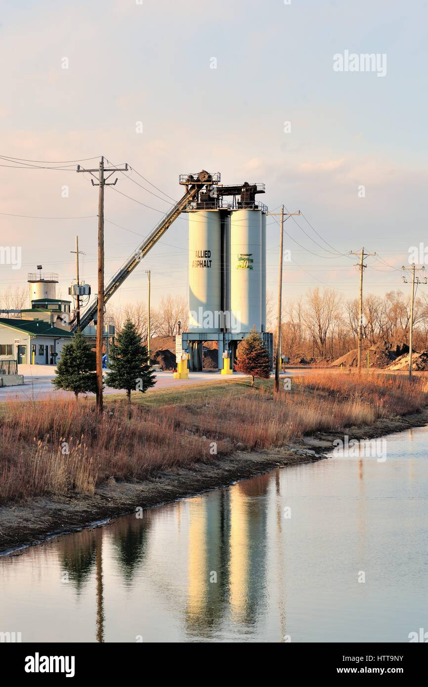 Storage tanks at an asphalt manufacturing business in an industrial setting near a retention pond in the Chicago - Stock Image