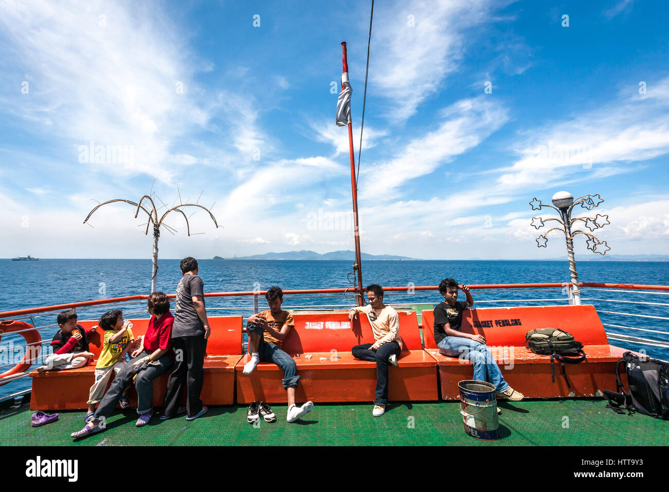 Passengers enjoying leisure time on the upper deck of the ferry during the Sunda Strait crossing. © Reynold - Stock Image