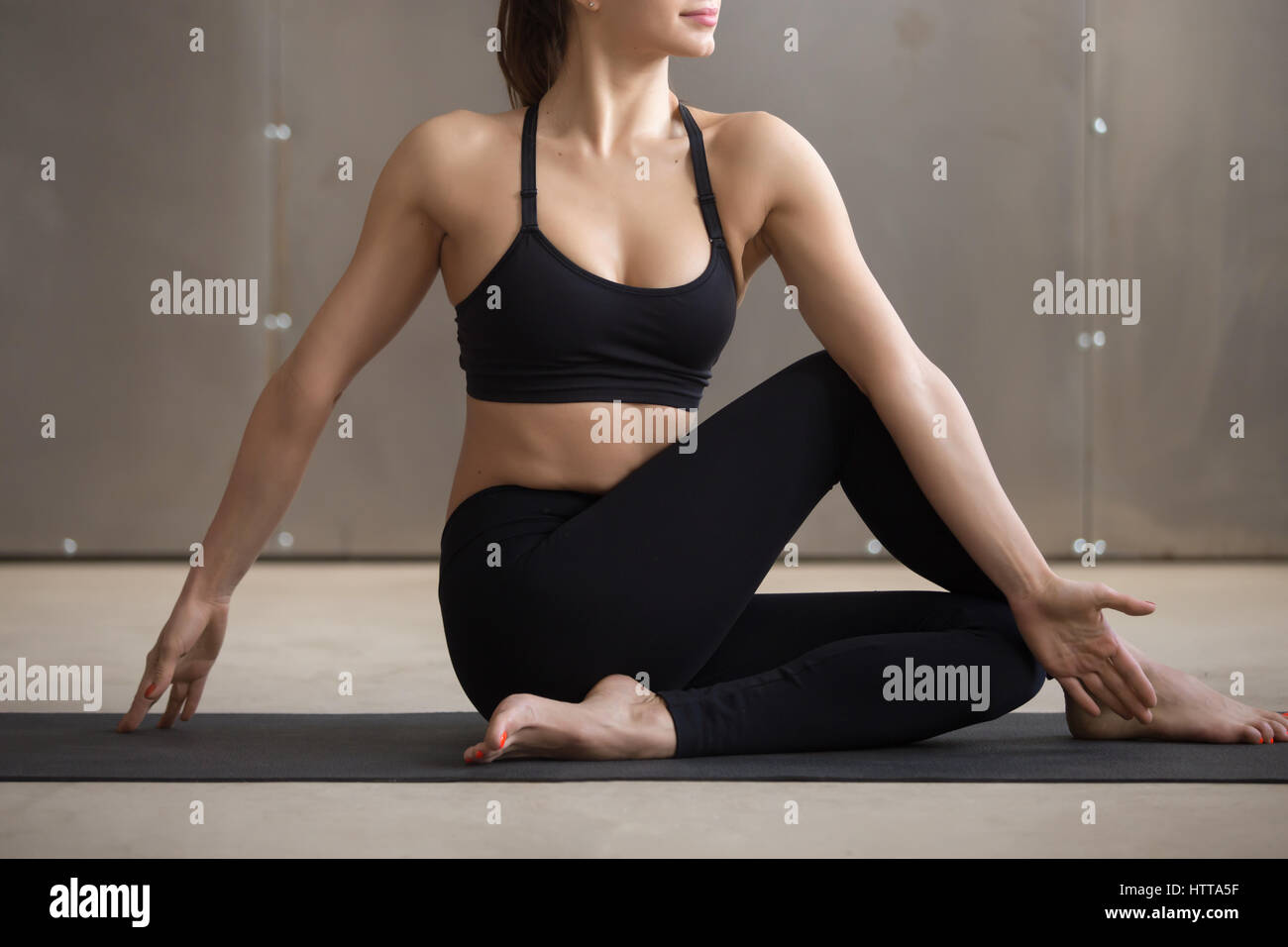 Young woman in Ardha Matsyendrasana pose, grey studio background - Stock Image
