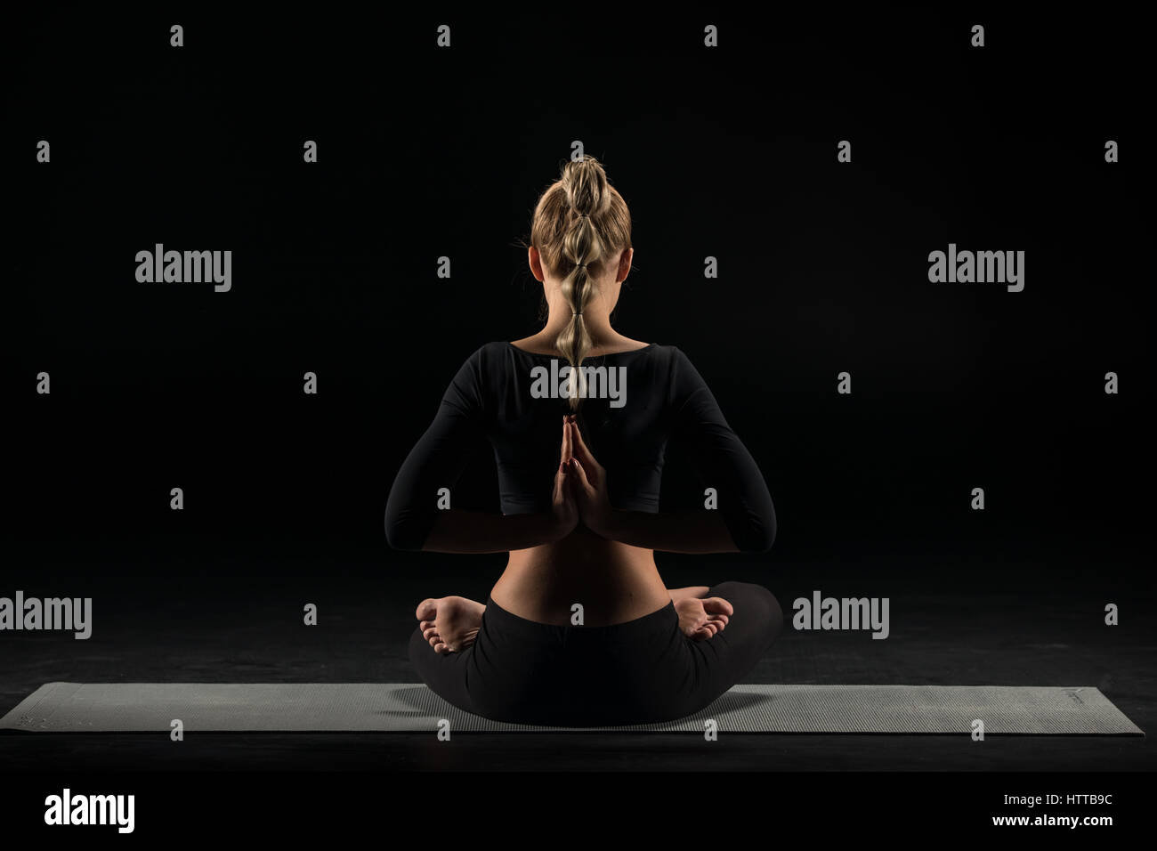 Woman sitting in yoga position - Stock Image