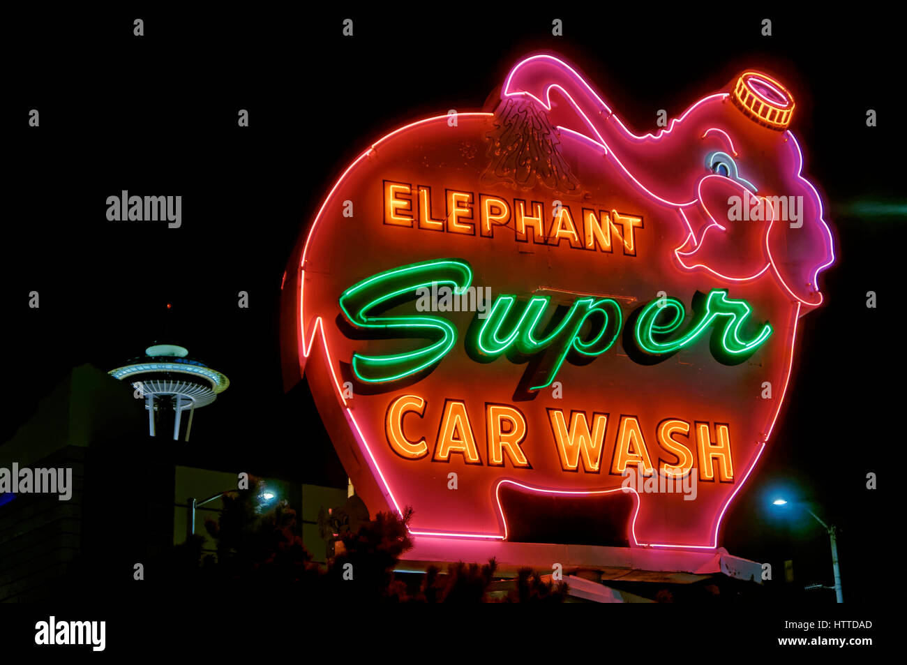 Rotating Elephant Super Car Wash neon sign at night with Space Needle in back in downtown Seattle, Washington state, - Stock Image