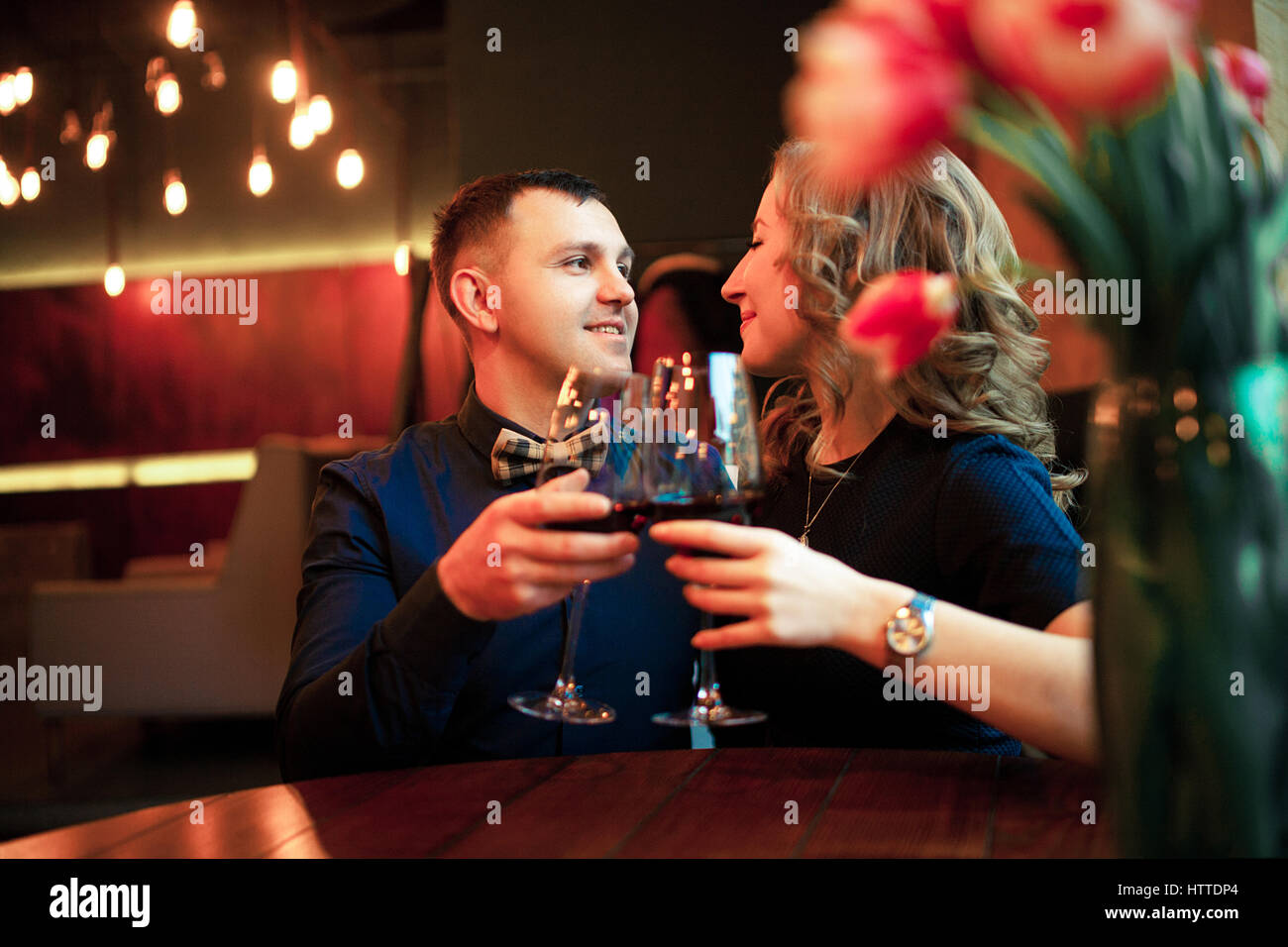 Young man clinks glasses with woman and makes her marriage proposal. They are sitting at the table. - Stock Image