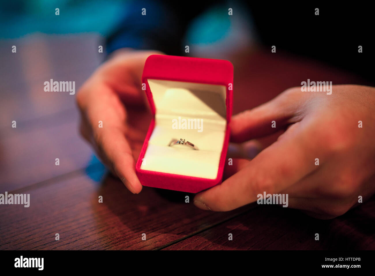 Man makes woman marriage proposal. He opened red jewelry case with engagement ring. He holds box in his hands. - Stock Image
