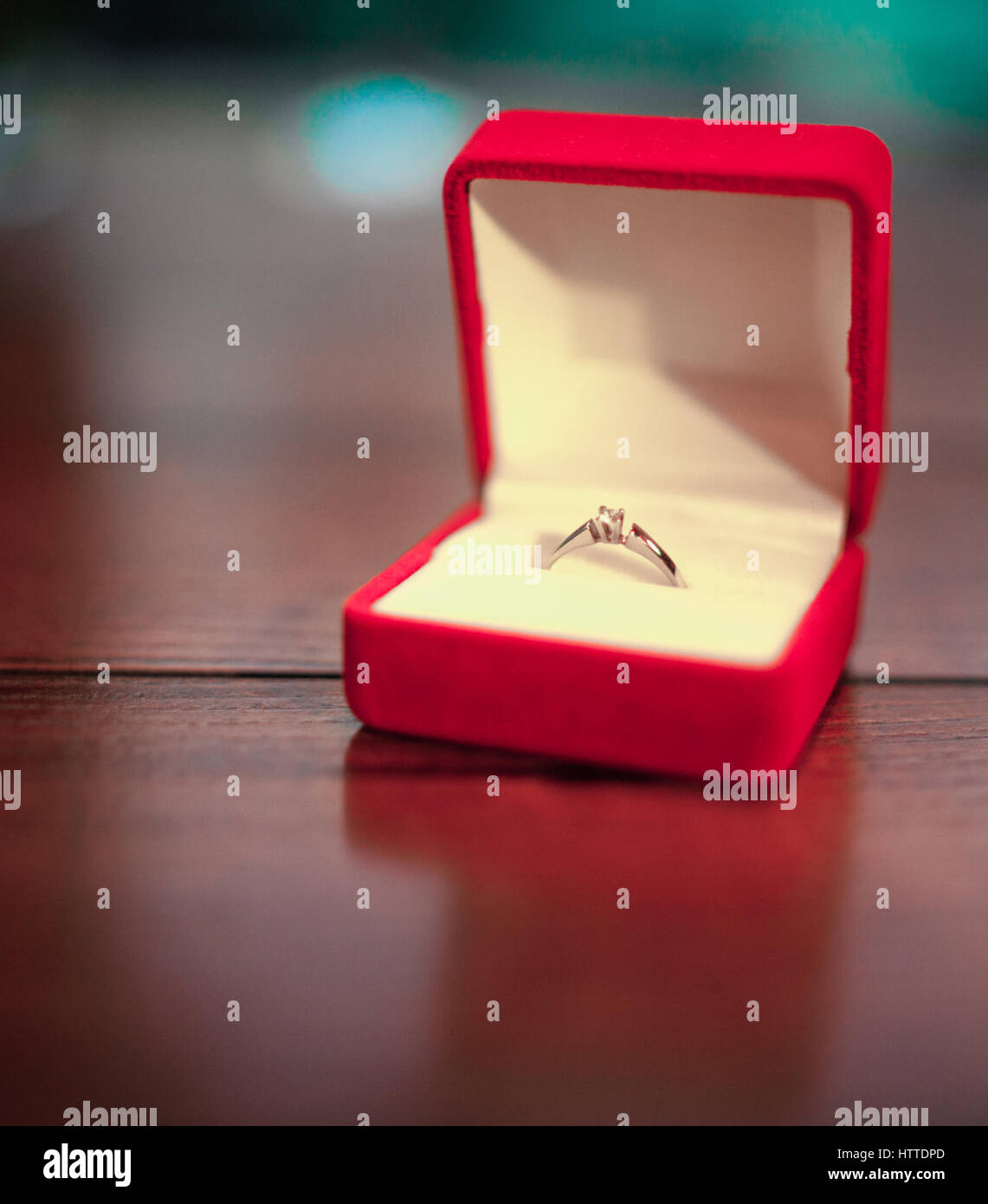 Opened red jewelry case with engagement ring on table. Gold ring with diamond. Close-up. - Stock Image