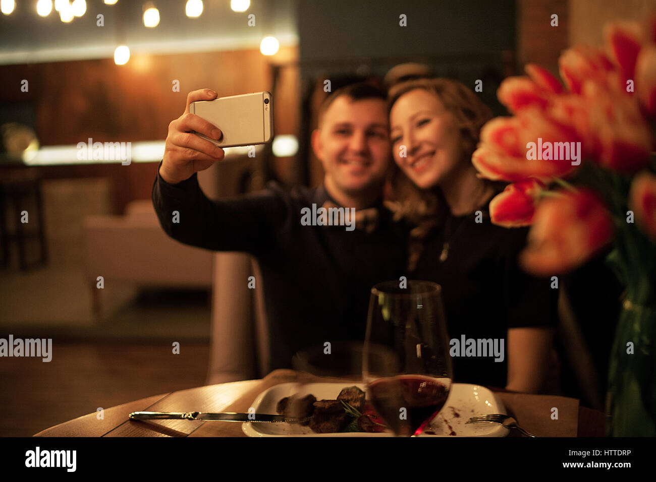 Young man and woman making selfy by smartphone in restaurant. Before them is table with food and glasses of wine. - Stock Image