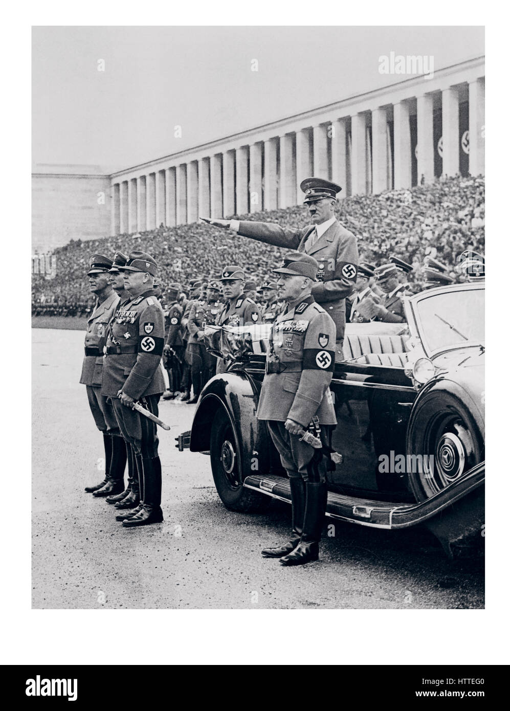 NUREMBERG RALLY Chancellor Adolf Hitler in uniform wearing a swastika armband, standing in his Mercedes car, saluting - Stock Image