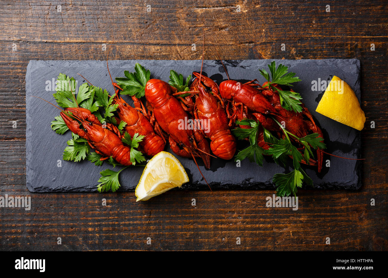 Red boiled crayfish with lemon serving size on stone slate on wooden background - Stock Image
