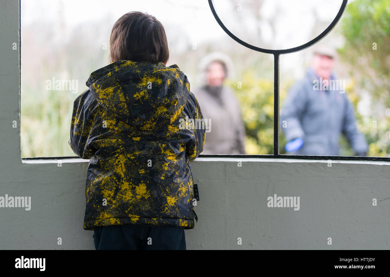 Inside looking out. Child looking out from a shelter to people walking past. - Stock Image