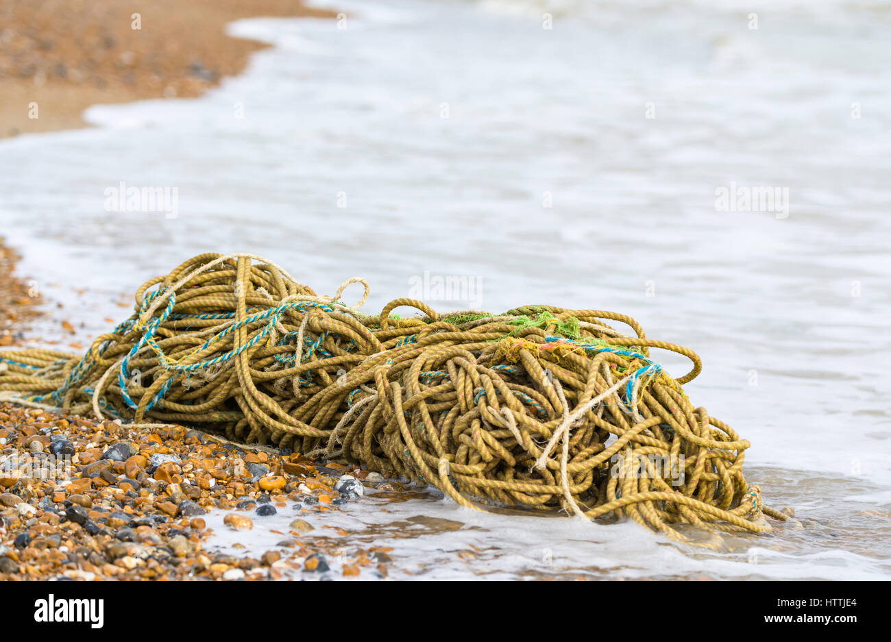 Discarded fisherman's rope washed up on a beach. - Stock Image