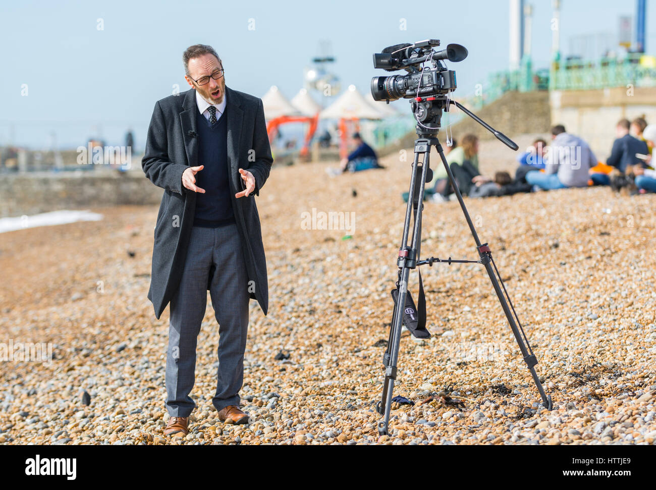News reporter on a beach making an outside broadcast for a television.news programme. - Stock Image
