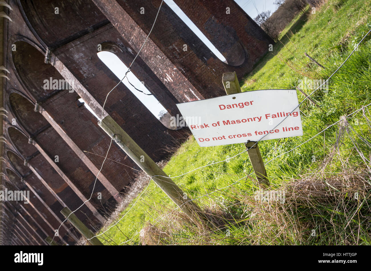 Sign warning 'Danger - Risk of masonry falling' sign at the Balcombe Viaduct, West Sussex, UK - Stock Image