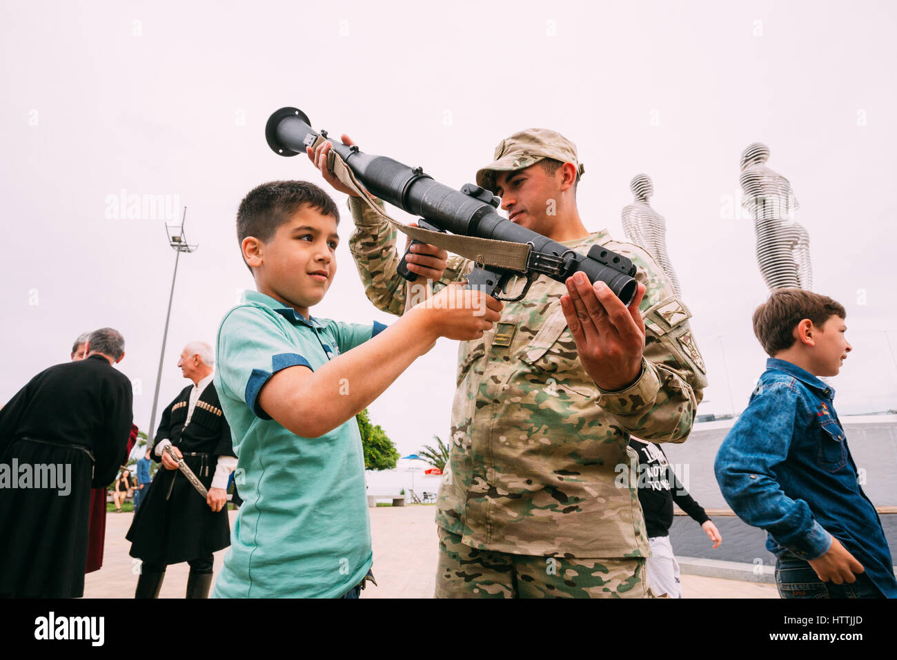 Batumi, Adjara, Georgia - May 26, 2016: Boy aiming rocket launcher at an exhibition of weapons during celebration - Stock Image