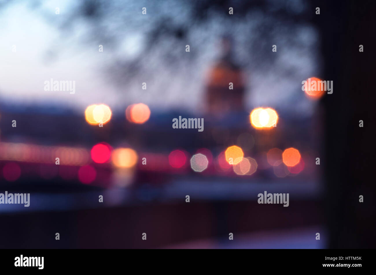 Unfocused cityscape of the embankment of river Neva and Saint Isaac's Cathedral on the back, light beams, winter - Stock Image