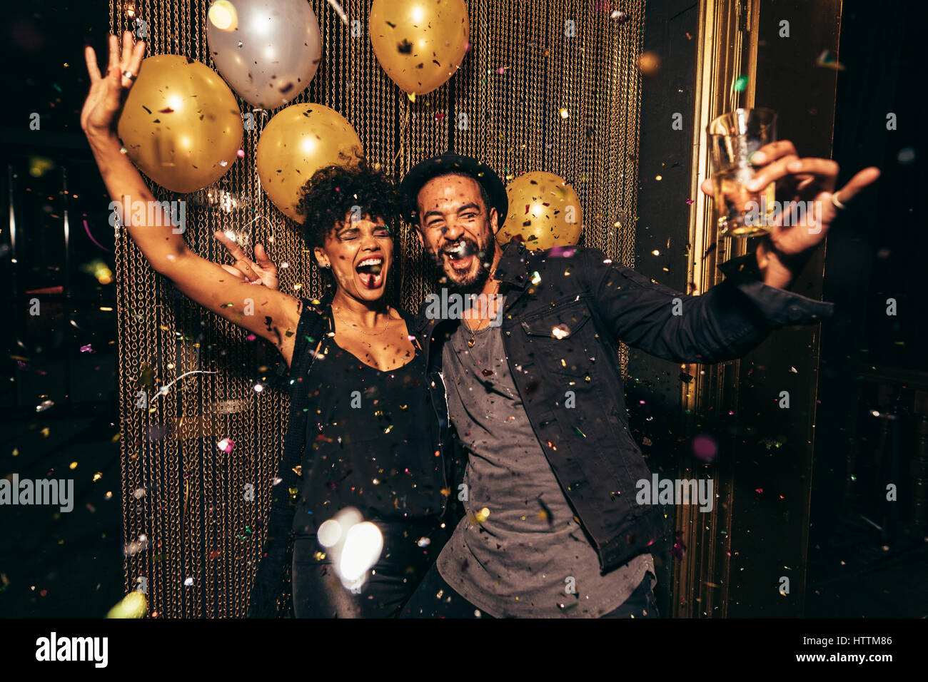 Shot of energetic couple dancing in the night club. Young man and woman having fun at pub party. - Stock Image