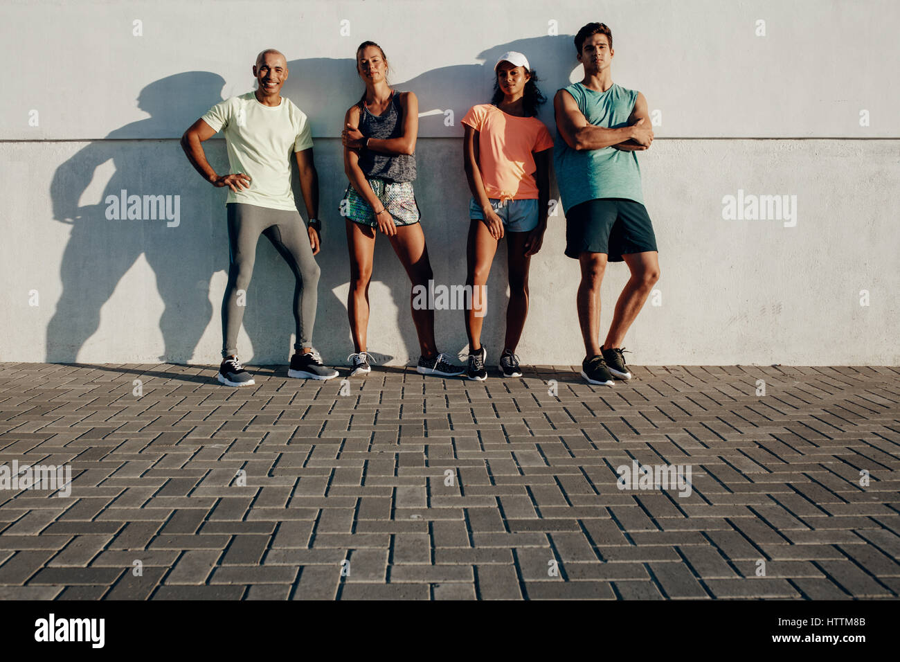Full length shot of young friends posing together. Group of fitness people standing by a wall outdoors. - Stock Image