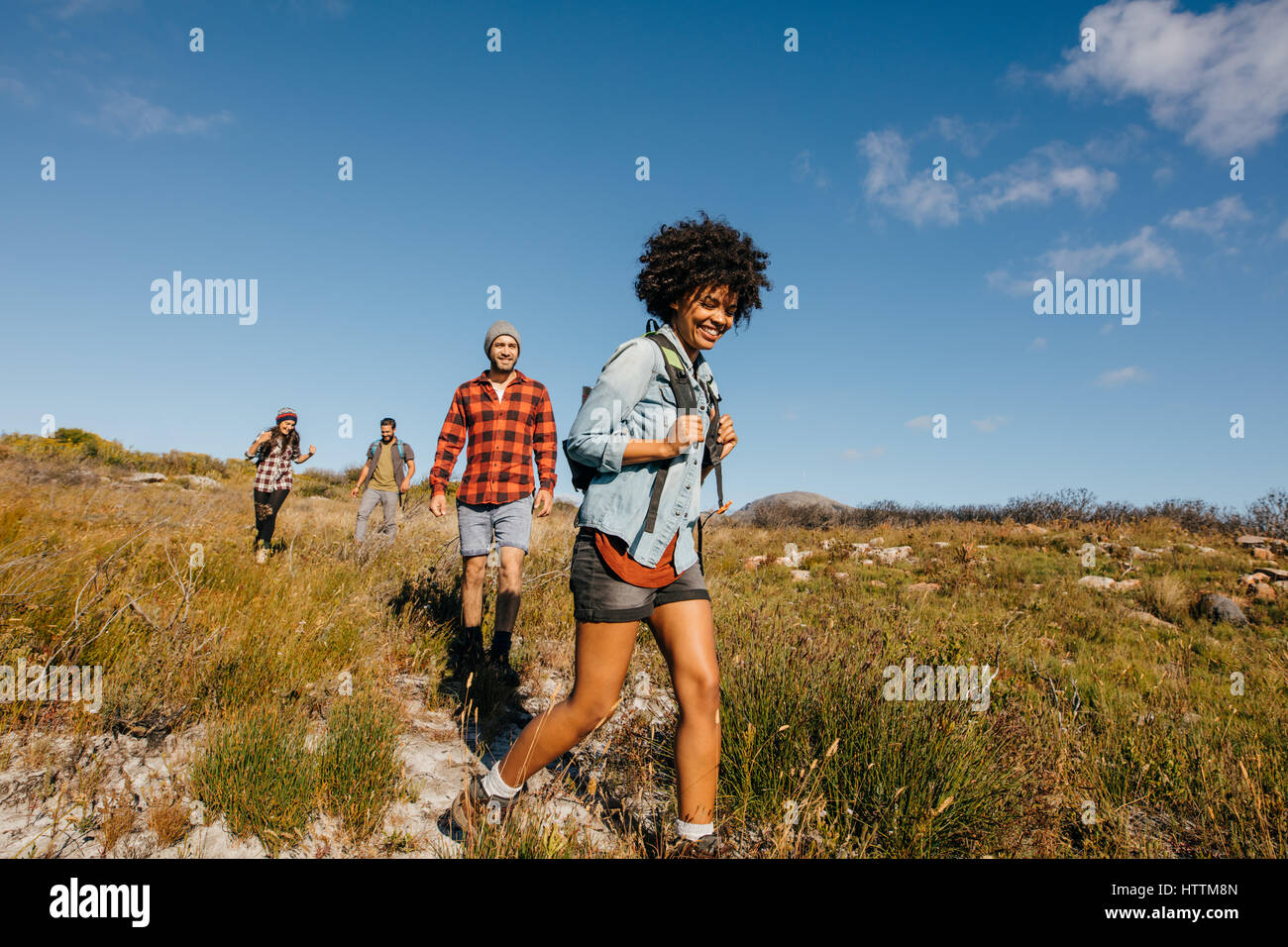 Group of young people on a hike through countryside together. Young friends hiking in nature. - Stock Image