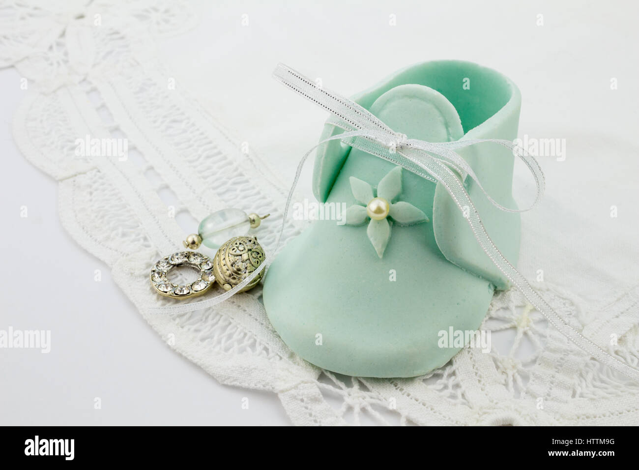 Blue fondant baby bootee on white lace background with silver charms for celebration invitation - Stock Image