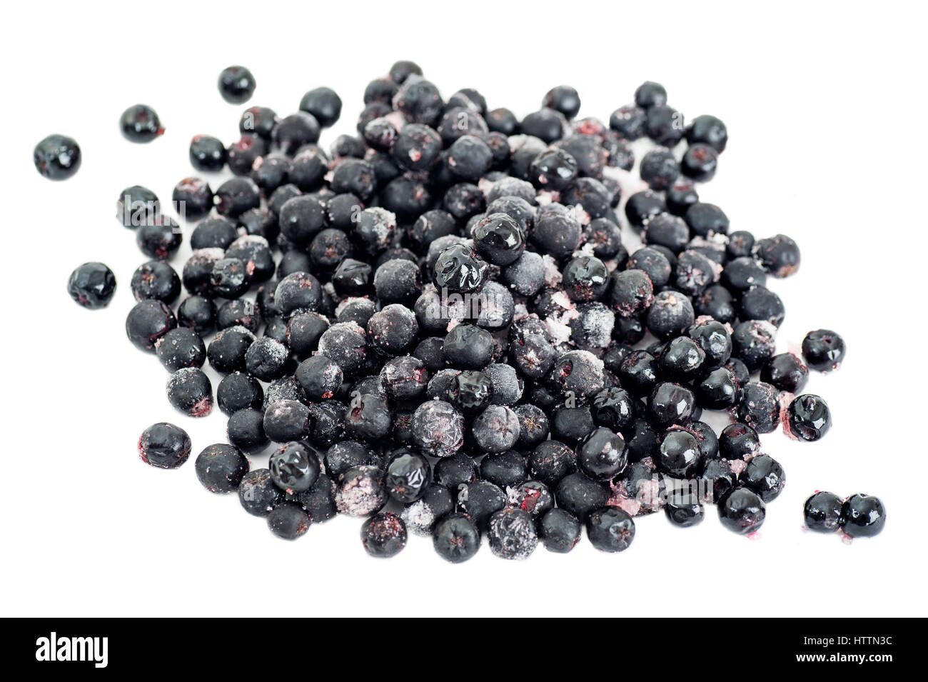 Organic frozen aronia berries on white background - Stock Image