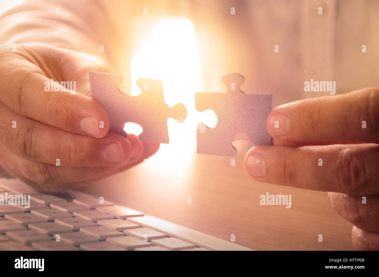 Closeup of man's hands holding puzzle pieces - Stock Image