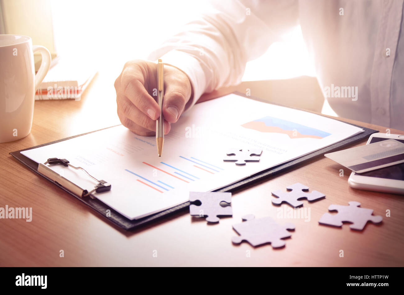 Businessman work with financial report at wooden office desk with puzzle pieces, smartphone, credit card and coffee - Stock Image