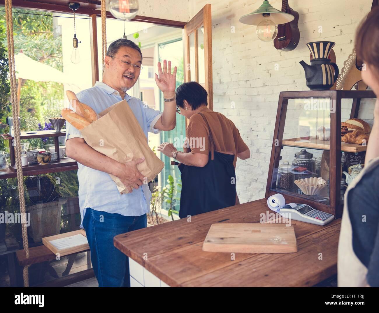 Customers bought bread waving goodbye - Stock Image