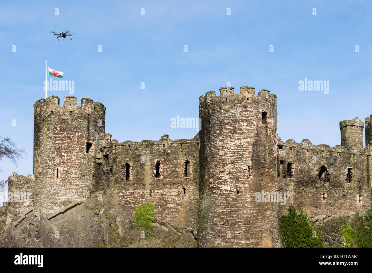 Conwy castle with Welsh flag and small drone flying above. Conwy, Wales, UK, Britain, Europe - Stock Image