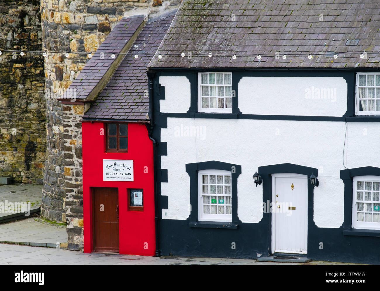 Small red Quay House is the Smallest House in Great Britain by the town walls on the quayside in Conwy, Wales, UK, - Stock Image