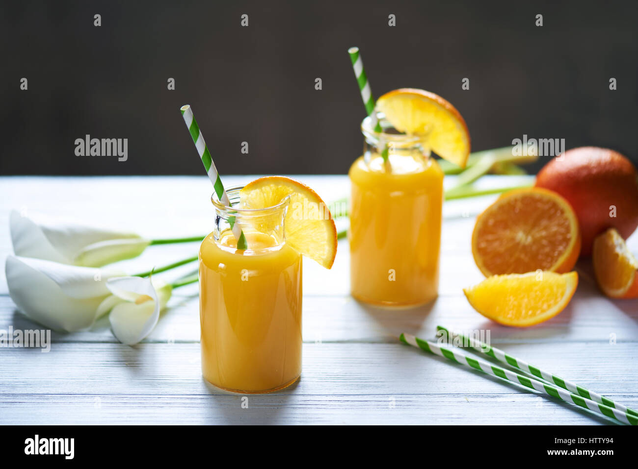 Fresh orange juice in the jar with straw and calla on white wood table. Vertical shot - Stock Image